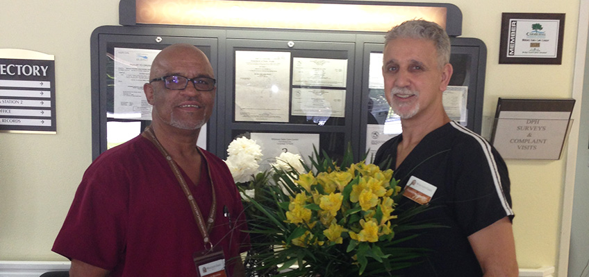 two male nurses smiling with one holding flowers