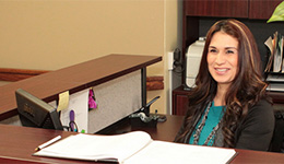 secretary sitting at her desk smiling