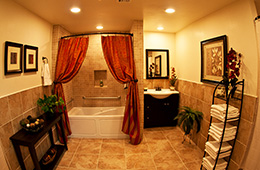 bathroom with bath, towels on a rack and ornate curtains and lighting