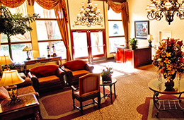 elaborate lobby area with chairs, carpeting and chandeliers