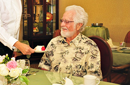 gray haired man sitting at a dining table being served cake