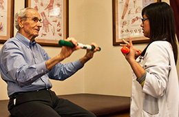 elderly man doing physical therapy with a stick, with help of a therapist