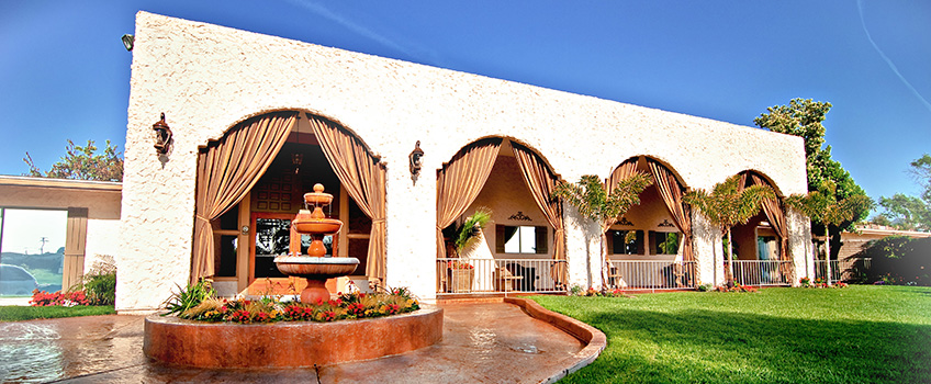 beautiful shot of the front of the building with high arches, a fountain and green grass