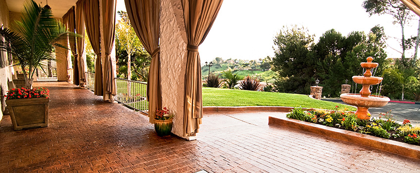 beautiful outdoor area with fountains and flowers and large curtains