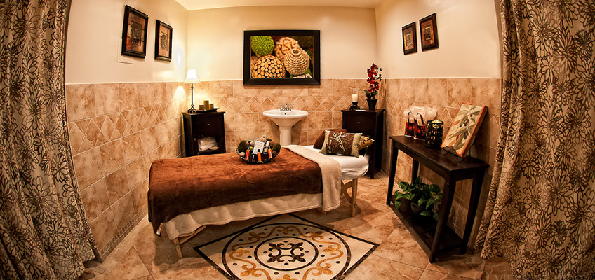 massage table in a spa room with nice tiling on the walls and floors and curtains