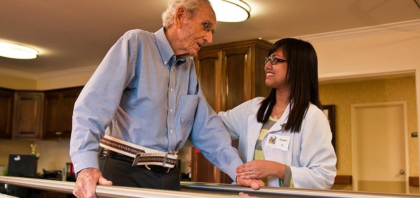 elderly man getting help with walking using parallel bars