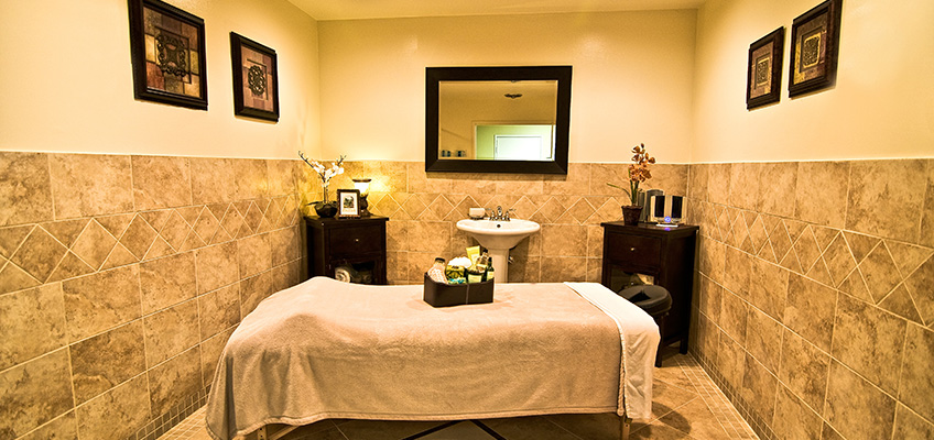 spa room with a massage table in the middle and nicely tiled walls