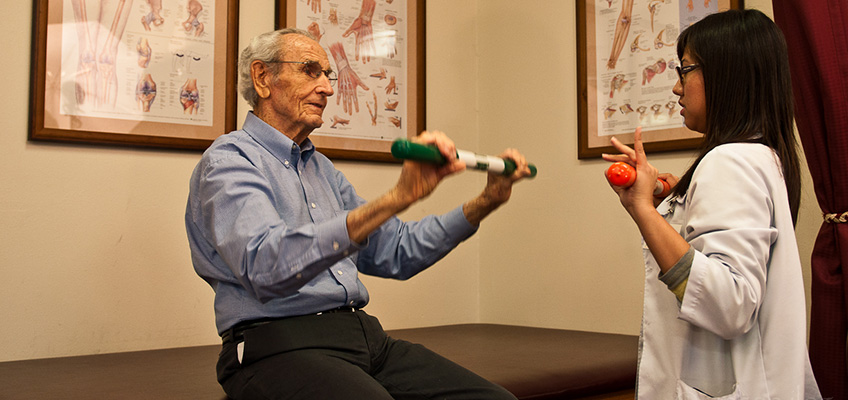 elderly man using a stick for physical therapy