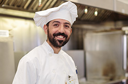 smiling chef wearing a chef hat
