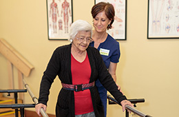 elderly woman using parallel bars for physical therapy