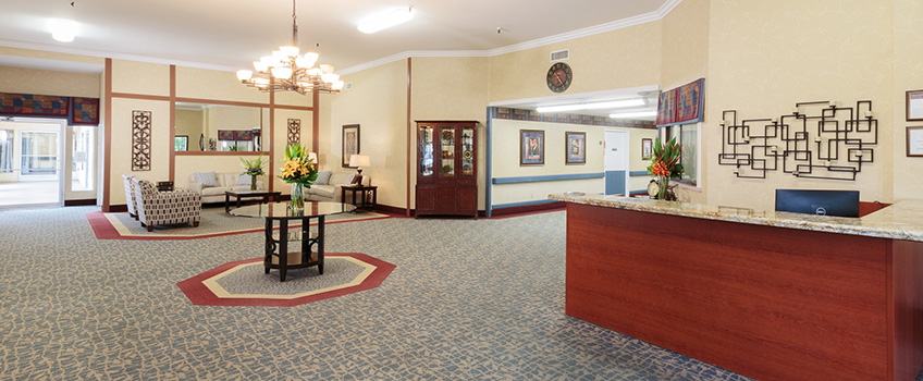 lobby area with wall art, chandelier and a desk