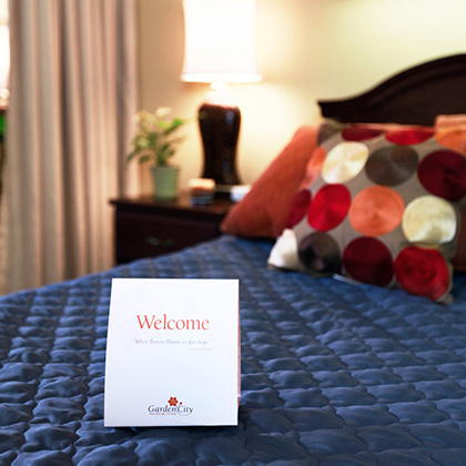 Resident room with welcome sign on bed sheets