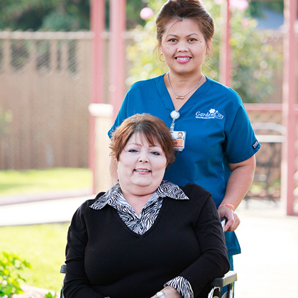 smiling nurse with smiling resident in wheel chair