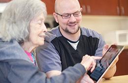 woman using an ipad with a nurse