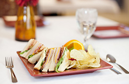 club sandwich with oranges served on a table