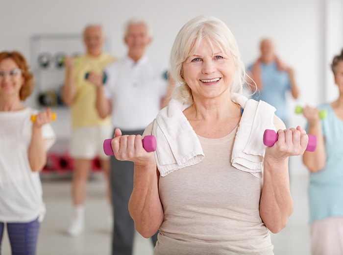 woman in group exercise class with small hand weights and a towel around her neck