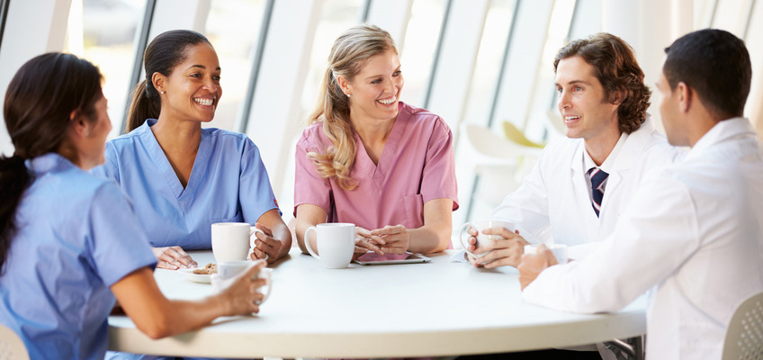 nurses and doctors sitting at a round table smiling and drinking coffee