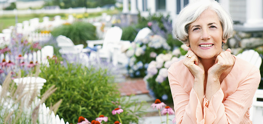 smiling silver haired woman sitting in a beautiful garden with a white picket fence