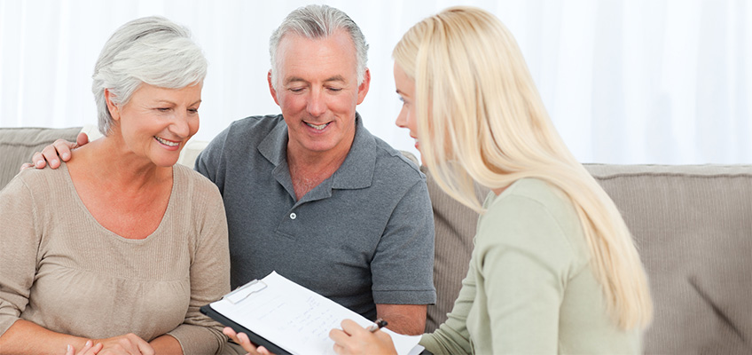 silver haired couple smiling and signing paperwork with a staff member