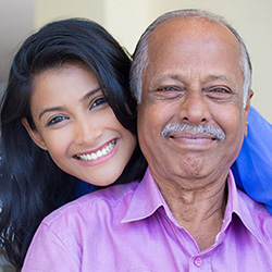 young woman smiling and hugging her grandpa