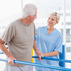 man using parallel walking bars for physical therapy with a therapist