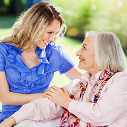 blonde woman in a blue shirt smiling at elderly woman with silver hair and a pink blouse