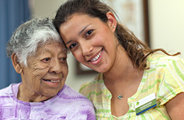 smiling woman staff with an elderly woman resident
