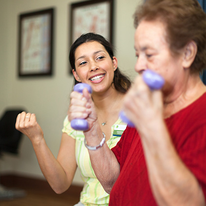 woman physical therapist helping woman resident with weights