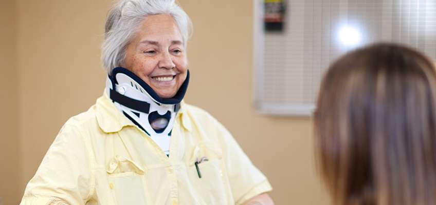 woman in a neck brace smiling with staff member
