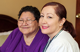 woman doctor and resident sitting and smiling with each other