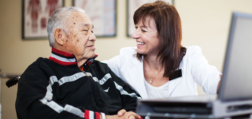 elderly man in a wheelchair and woman doctor smiling with each other