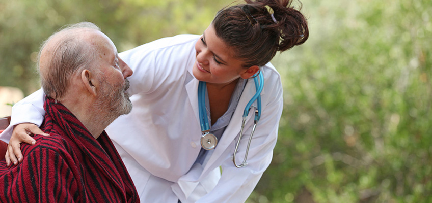 doctor leaning down talking to resident outdoors