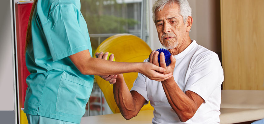 man working with hand weights with therapist