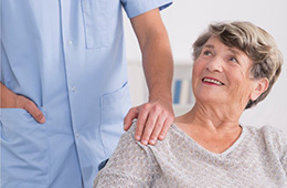 nurse placing her hand on a resident's shoulder