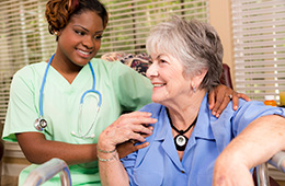 nurse lovingly putting her arms around a smiling resident