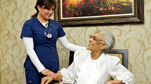 nurse holding the hand of a resident