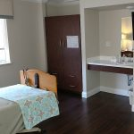 single occupancy room with sink & a flat screen TV