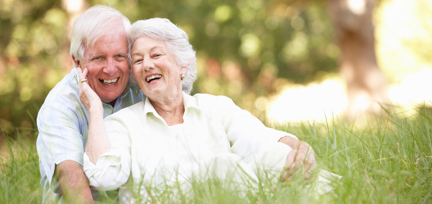 smiling white haired couple sitting in the grass