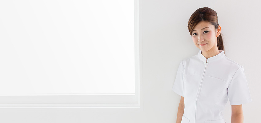 asian nurse smiling in a white room