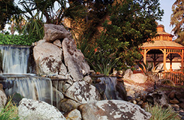 a waterfall and a gazebo area during sunset