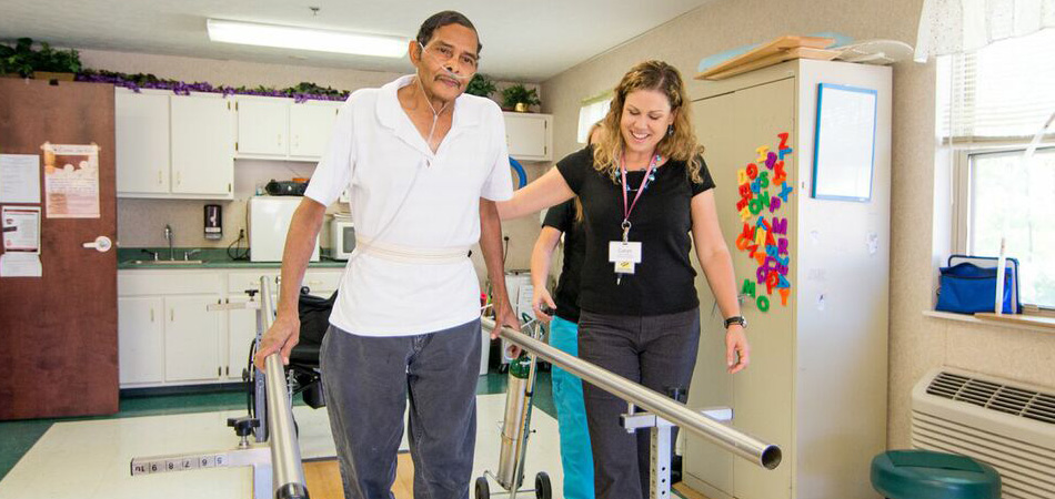 male resident working on parallel bars with a therapist
