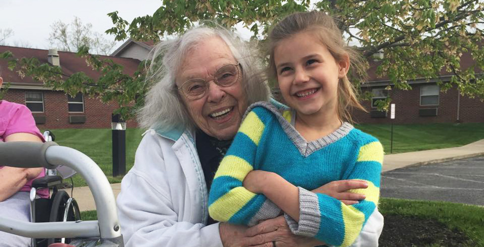 Grandma hugging her granddaughter, both are smiling widely