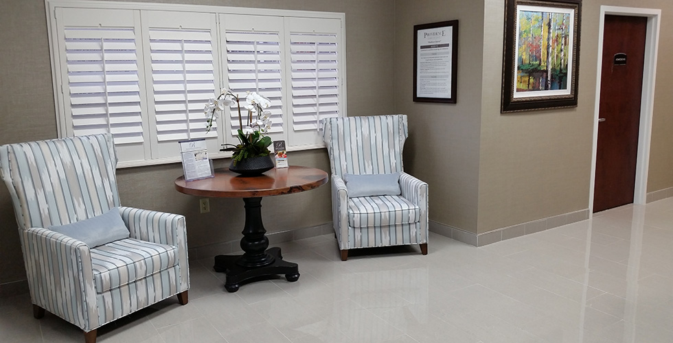 beautifully upholstered chairs in the lobby also decorated with fresh flowers and plantation shutters