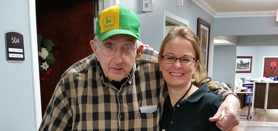 resident wearing a John Deere cap with his arm around the should of a nurse