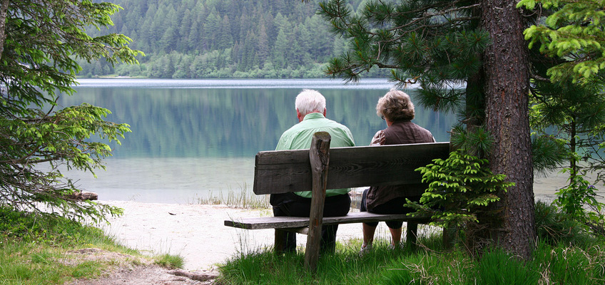 Elderly couple sitting on a bench next to a lake surrounded by trees