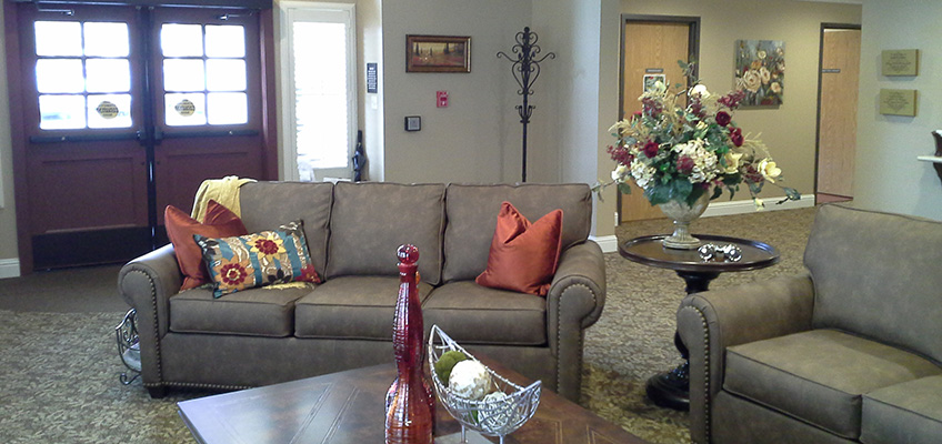 Leather couches, decorative vases & pillows, and flower arrangement on table