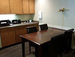300 Main community break area with cabinets, table and chairs, microwave and sink