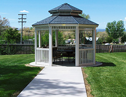 beautiful white gazebo with a sidewalk leading to it