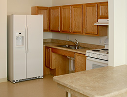 a kitchen with wooden cabinets and a white fridge