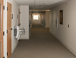 a long hallway with some water fountains on the side